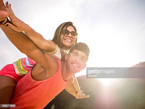 Latin American couple having fun while piggybacking.