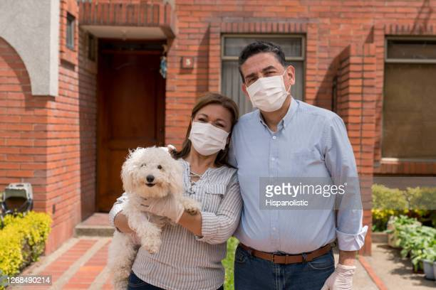 latin american couple outside their house wearing facemasks and holding their pet - biosecurity stock pictures, royalty-free photos & images
