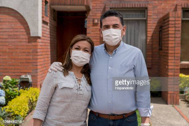 latin american couple outside their house wearing facemasks - biosecurity stock pictures, royalty-free photos & images