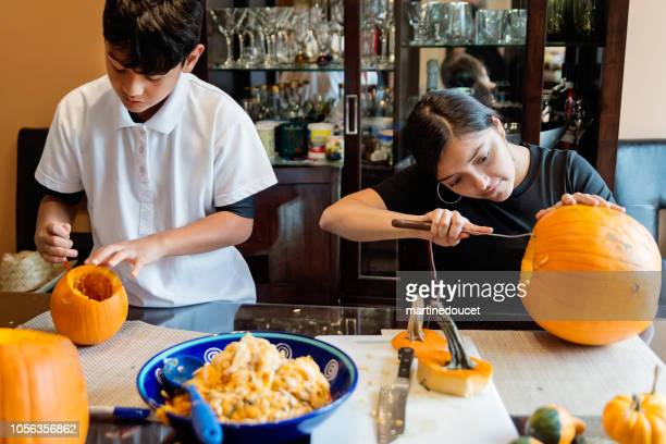 Latin American family carving pumpkins for Halloween
