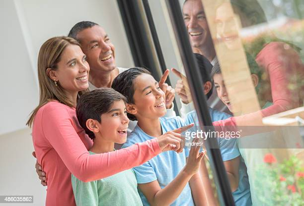 Latin American family looking through window at home