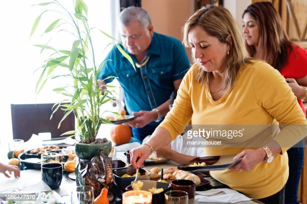 Latin American family putting food on plates at family gathering.