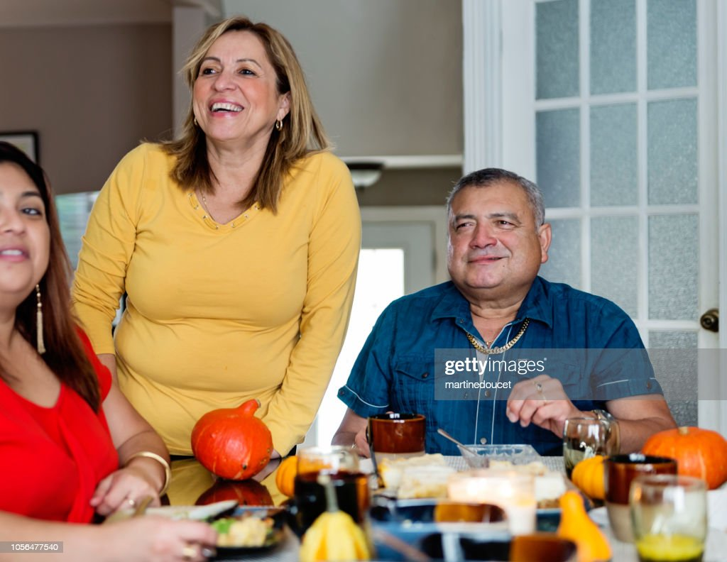 Latin American family putting food on plates at family gathering. : Stock Photo