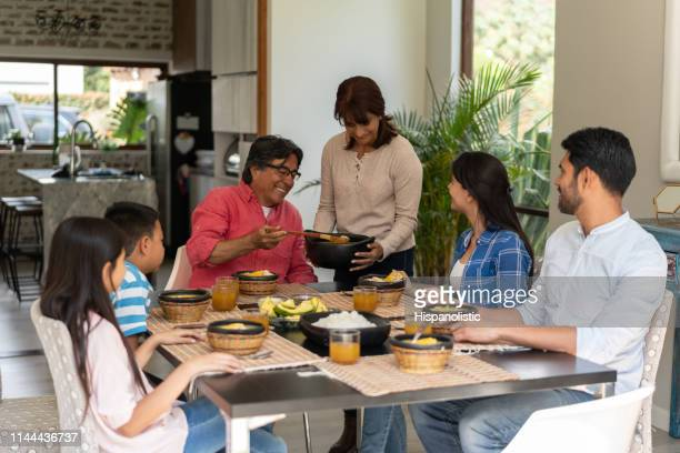 latin american family serving chicken on delicious ajiaco all smiling - rice food staple stock pictures, royalty-free photos & images