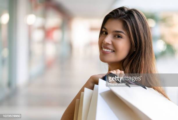 Latin american female at the mall looking at camera smiling while holding bags over her shoulder