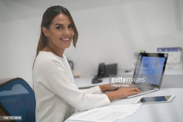 Latin american female working at her office on laptop while looking at camera smiling