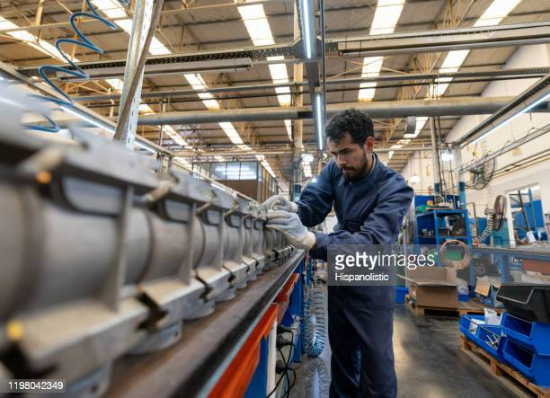 latin american focused young man working at a manufacturing water pump factory - production line stock pictures, royalty-free photos & images