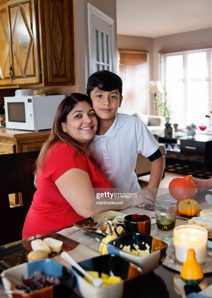Latin American godmother and godchild portrait at meal time. : Stock Photo