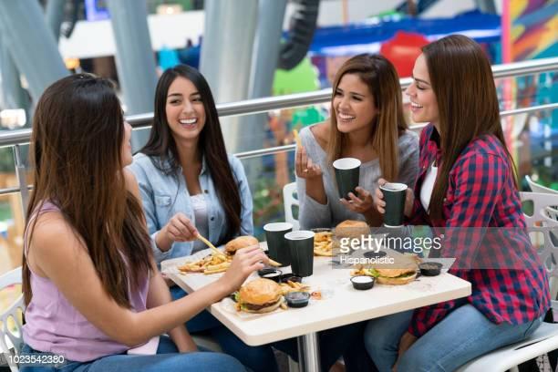 América Latina grupo de amigas que se divierten en el mall, comiendo hamburguesas en el patio de comidas al hablar