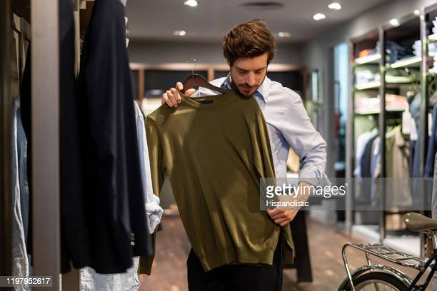 latin american guy trying out a sweater on top at a men's clothing store - clothing stock pictures, royalty-free photos & images