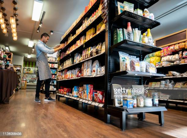 latin american handsome salesman at a groumet food store organizing the shelf - arranging stock pictures, royalty-free photos & images