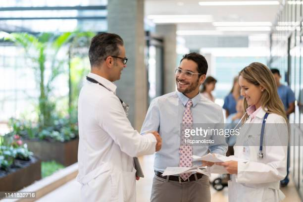 latin american hospital supervisor handshaking with male doctor at the hospital while holding some documents - manager stock pictures, royalty-free photos & images