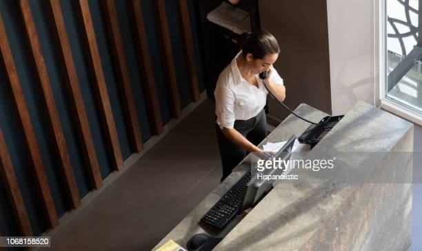 latin american hotel receptionist taking a phonecall - hotel stock pictures, royalty-free photos & images