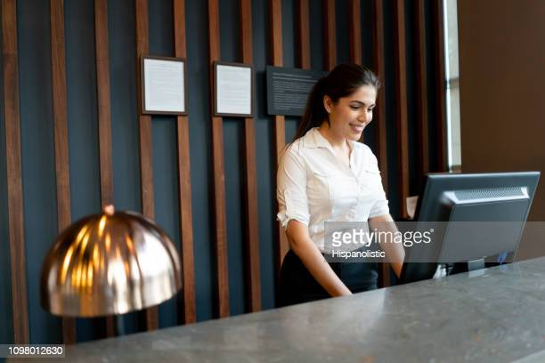 latin american hotel receptionist working behind counter smiling while looking at computer screen - hotel stock pictures, royalty-free photos & images