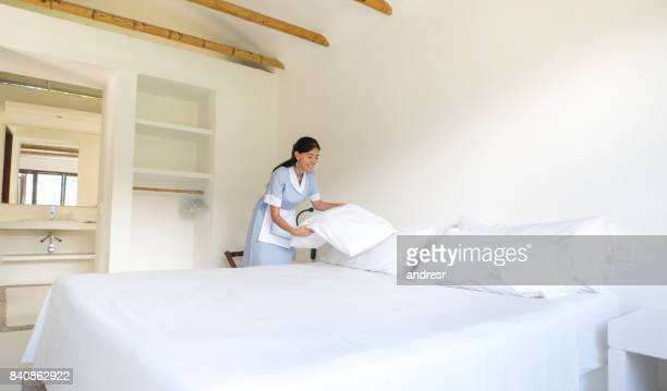 latin american housekeeper making the bed at a hotel - bedclothes stock pictures, royalty-free photos & images