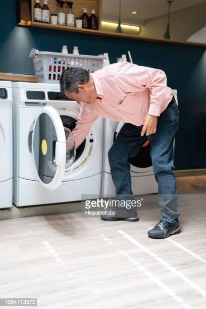 latin american male auf ein self-service-wäsche beladen der waschmaschine - weichspüler stock-fotos und bilder