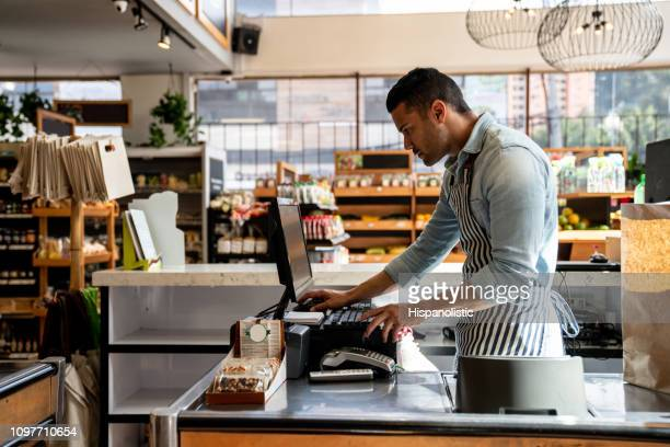 latin american male cashier at the supermarket looking something on system looking serious - cash register stock pictures, royalty-free photos & images