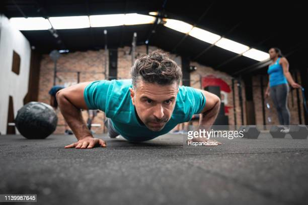 latin american man at the gym doing push ups - hispanolistic stock photos and pictures