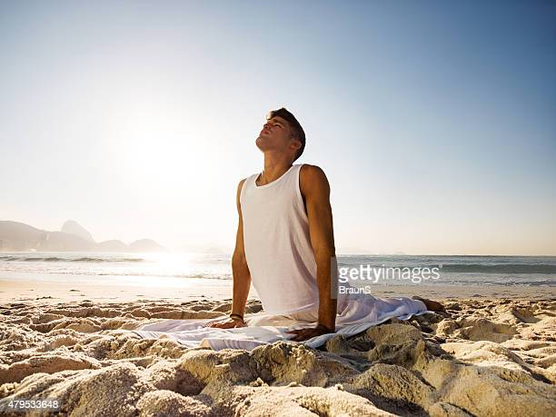Latin American man in cobra pose at the beach.