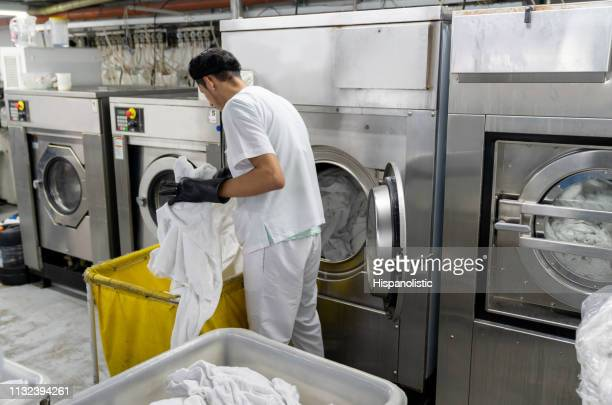 latin american man loading washing machine with dirty bed sheets at an industrial laundry service - dry cleaner stock pictures, royalty-free photos & images