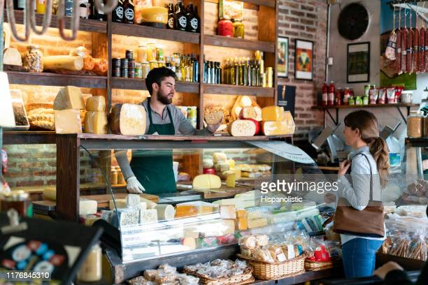 latin american man working at a delicatessen suggeting a type of cheese to female customer - delicatessen stock pictures, royalty-free photos & images