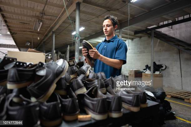 latin american man working at a shoe factory inspecting the sole of shoes very focused - shoe factory stock pictures, royalty-free photos & images