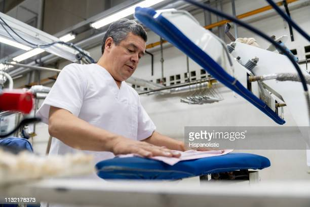 latin american mature man at a laundromat ironing clothes with a steamer - dry cleaner stock pictures, royalty-free photos & images