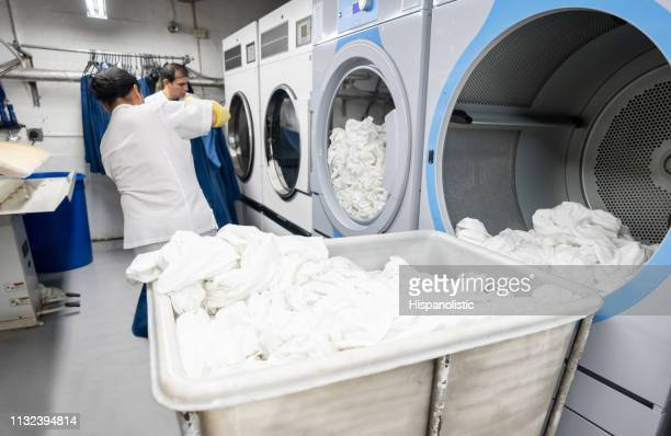 latin american men working together loading a washing machine at a laundry service - laundry stock pictures, royalty-free photos & images