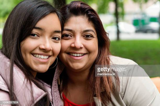 Latin American mother and tennage daughter portrait outdoors.