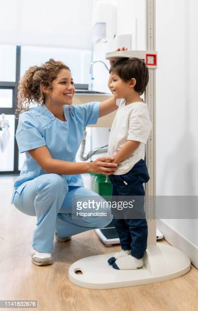 latin american nurse measuring a pediatrics patient checking hos growth progress both smiling - cute nurses stock pictures, royalty-free photos & images
