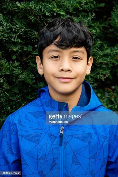 Latinamerikanska preteen pojke porträtt utomhus.