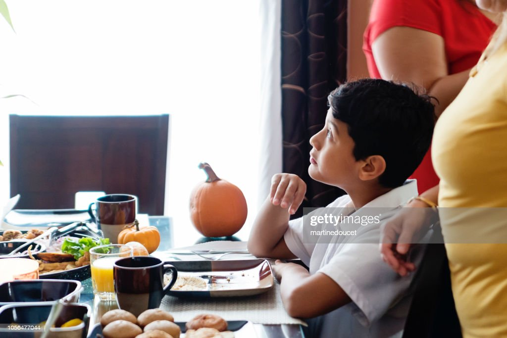 Latin American preteen boy sitting at the family table. : Stock Photo