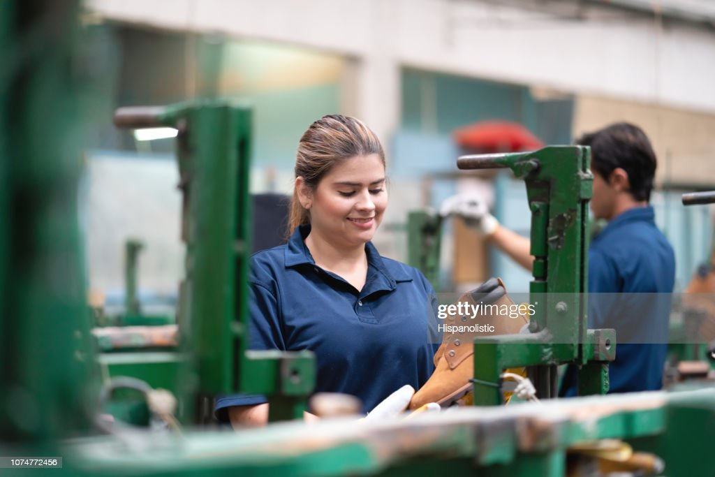 Latin american pretty cobbler at a shoe factpry producing boots : Stock Photo