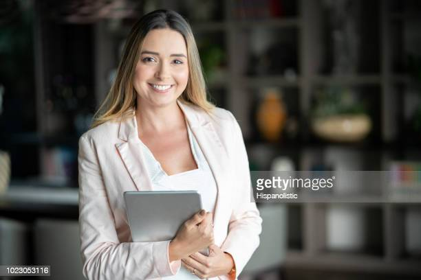 latin american real estate agent holding a tablet and looking at camera smiling - saleswoman stock photos and pictures