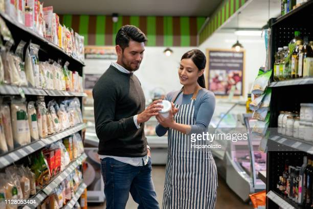 latin american sales clerk at a supermarket suggesting a product to male customer smiling - assistant stock pictures, royalty-free photos & images