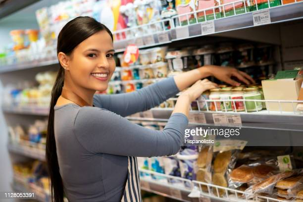 Latin american sales clerk organizing products on shelve while facing camera smiling