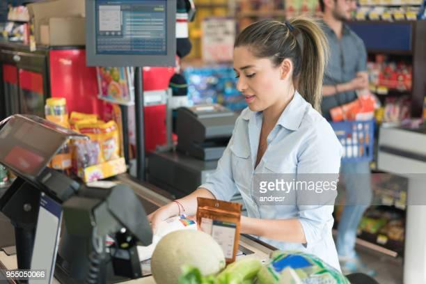 Lateinamerikanische Verkäuferin Registrierung der Produkte auf System durch das Scannen von Barcodes auf Produkte, die auf der Suche konzentrierte sich