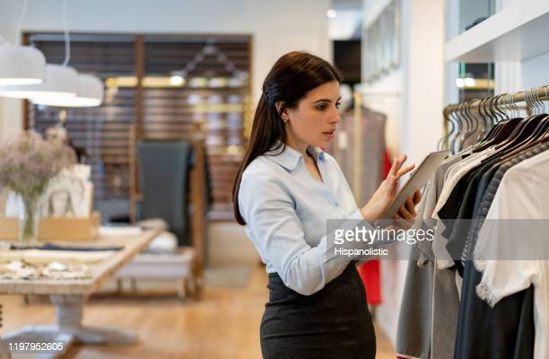 タブレットを使って在庫をチェックする衣料品店で働くラテンアメリカ人のセールスウーマン - 百貨店 ストックフォトと画像