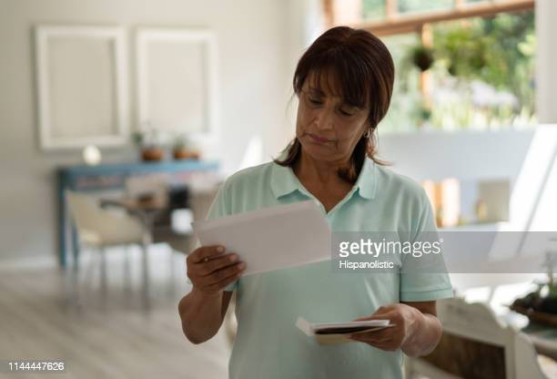 Latin american senior woman at home going over her mail