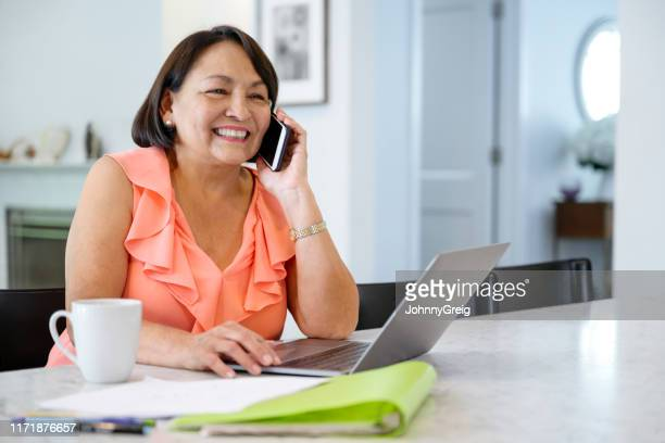 latin american senior woman hearing good news on smart phone - ringing stock pictures, royalty-free photos & images
