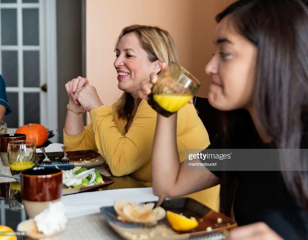 Latin American senior woman sitting at table at family gathering. : Stock Photo