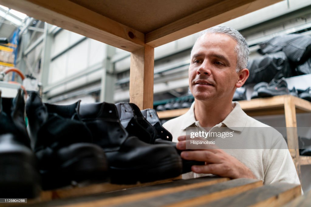 Latin american shoe maker checking the boots on shelf smiling : Stock Photo