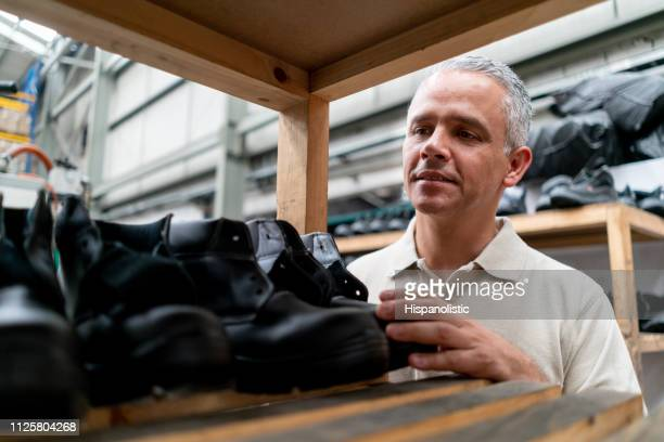 Latin american shoe maker checking the boots on shelf smiling