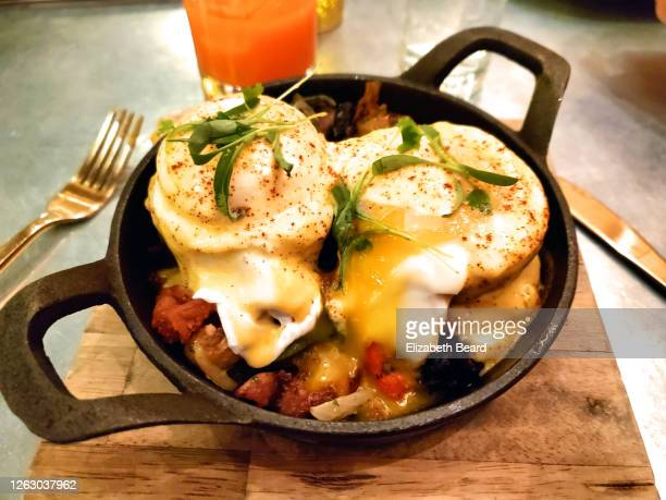 latin american style eggs benedict in cast iron skillet - chorizo stock pictures, royalty-free photos & images