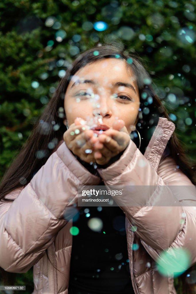 Latin American teenage girl blowing confettis outdoors. : Stock Photo