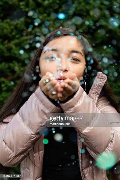 Latin American teenage girl blowing confettis outdoors.