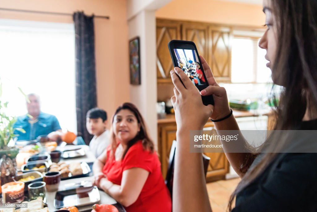 Latin American teenager taking photo of the family at meal time. : Stock Photo