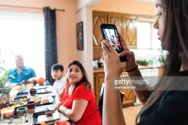 Latin American teenager taking photo of the family at meal time.