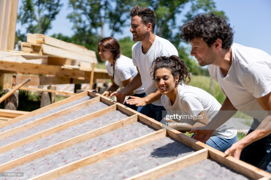 Latin american volunteers working hard at a charity construction project : Stock Photo