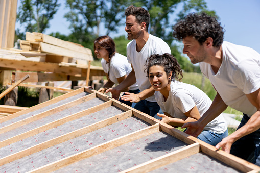 Latin american volunteers working hard at a charity construction project 1190692184
